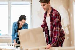 准备墙纸的年轻人,当谈话与他的女朋友时 免版税库存图片