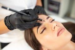 准备她的客户眼眉的被证明的美容师 库存照片