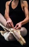 准备她的芭蕾舞鞋的芭蕾舞女演员 库存图片