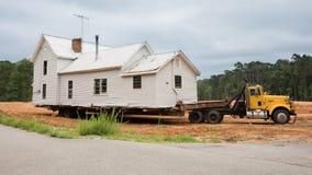 准备好一个老的房子在一辆平床卡车后被移动 免版税库存照片