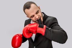 准备好严肃和恼怒的年轻人战斗 他拿着在嘴的钩子 集中人 他佩带衣服和红色 免版税库存图片