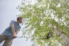 准备好低角度的观点的年轻人击中在高尔夫球场的高尔夫球 库存图片