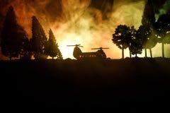准备好军用直升机的剪影从冲突区域飞行 有起动在沙漠的直升机的装饰的夜英尺长度与 免版税图库摄影