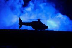 准备好军用直升机的剪影从冲突区域飞行 有起动在沙漠的直升机的装饰的夜英尺长度与 库存照片