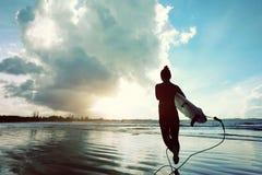 准备好女子的冲浪者冲浪在海滩 免版税库存图片