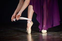 准备好年轻的芭蕾舞女演员一个古典舞蹈 女孩佩带的点穿上鞋子在黑暗的背景的特写镜头 库存照片