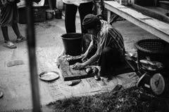 准备好未认出的老人毁坏的鱼卖在泰国传统市场Prachuapkhirikhan省,泰国 免版税图库摄影