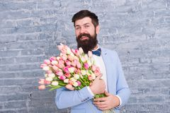 准备好浪漫日期的强壮男子 等待的亲爱的 甜心的郁金香 人穿着考究的穿戴无尾礼服蝶形领结举行 免版税图库摄影