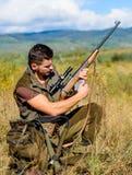 准备好猎人卡其色的衣裳寻找自然背景 狩猎射击战利品 与寻找动物的步枪的猎人 库存图片
