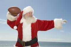 准备好的圣诞老人投掷橄榄球球 免版税图库摄影