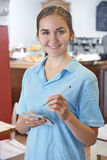 准备好的女服务员接受在咖啡馆的命令 免版税库存图片