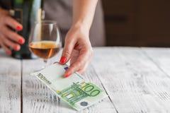 准备好的妇女支付与欧洲钞票的威士忌酒 免版税图库摄影
