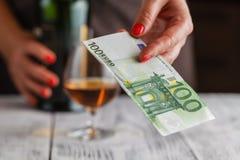 准备好的妇女支付与欧洲钞票的威士忌酒 库存照片