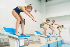 准备好的孩子跳进体育游泳池 开玩笑运动 库存图片