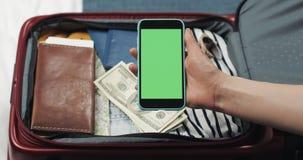 准备好的年轻女人旅行 拿着有绿色屏幕的她智能手机在手提箱背景 o 股票视频