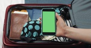 准备好的年轻女人旅行 拿着有绿色屏幕的她智能手机在手提箱背景 o 股票录像