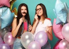 准备好的当事人 时髦的夏天成套装备、纸玻璃和获得的气球的两个女孩乐趣和庆祝生日 免版税库存照片