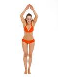 准备好的泳装的愉快的妇女跳跃在水中 免版税库存图片
