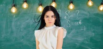 准备好的老师开始教训,拷贝空间 有长的头发的妇女在白色女衬衫在教室站立 精华学校 免版税库存图片