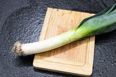 准备好的韭葱被切开和被烹调 在一个木切板的韭葱 免版税库存照片