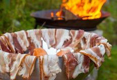 准备好的香肠和的烟肉烤在阵营火 库存照片