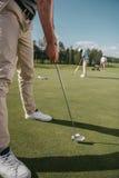 准备好的高尔夫球运动员击中在高尔夫球场的一个球在白天 免版税库存照片
