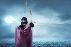 准备好的hijab的年轻亚裔回教妇女射击箭头 图库摄影