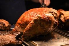 准备好肉多汁金黄整个烘烤火鸡的联接雕刻与叉子和手在背景中 免版税库存图片
