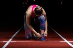 准备好运动员女孩尝试的跑鞋在轨道的种族 库存图片