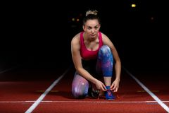 准备好运动员女孩尝试的跑鞋在轨道的种族 免版税库存图片
