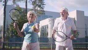 准备好逗人喜爱的成熟的夫妇打在网球场的网球 拿着球拍和球的妇女通过 股票视频