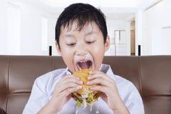 准备好逗人喜爱的男孩在家咬住汉堡 库存照片