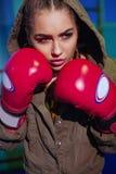 准备好年轻女性的拳击手战斗在老皮革拳击手套 性感的体育穿戴的健身愉快的白肤金发的女孩与完善的身体 库存照片