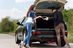 准备好年轻的夫妇改变轮胎 库存照片
