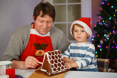 准备姜饼曲奇饼房子的父亲和小儿子 免版税图库摄影