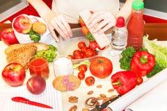 准备学校午餐箱子的一个少妇的手 免版税库存图片