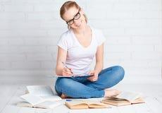 准备家庭作业的愉快的女学生,为检查wi做准备 图库摄影