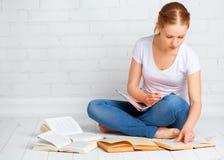准备家庭作业的愉快的女学生,为检查wi做准备 库存图片