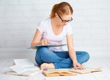 准备家庭作业的愉快的女学生,为检查wi做准备 免版税库存图片