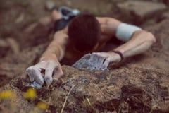 准备对在他的途中的接下来的步骤的攀岩运动员由上面决定 库存图片