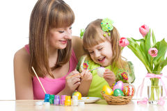 准备对复活节假日和用刷子着色鸡蛋的愉快的母亲和儿童女儿 免版税库存图片