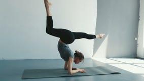 准备对手倒立分裂姿势的健康瑜伽妇女 行使在演播室的健身生活方式舒展美好的身体 股票录像