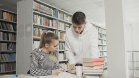 准备对检查的两位白种人大学生在图书馆里 股票视频