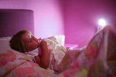 准备对睡觉的小女孩在床上 库存照片
