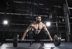 准备对deadlift杠铃在的肌肉赤裸上身的人喂 免版税图库摄影