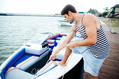 准备小船的年轻英俊的人开始旅途 库存照片