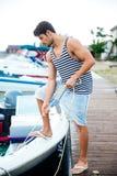 准备小船的年轻英俊的人开始旅途 免版税库存图片