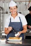 准备巧克力卷的愉快的厨师 图库摄影