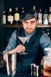 准备干燥马蒂尼鸡尾酒和服务对客户的英俊,葡萄酒微笑的侍酒者 免版税库存图片