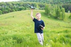 准备微笑的年轻的男孩发射RC飞行 背景美好的做的本质向量 库存图片